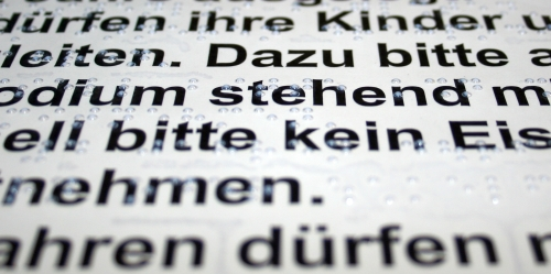 Nahaufnahme Braillefolie mit Schwarzschrift